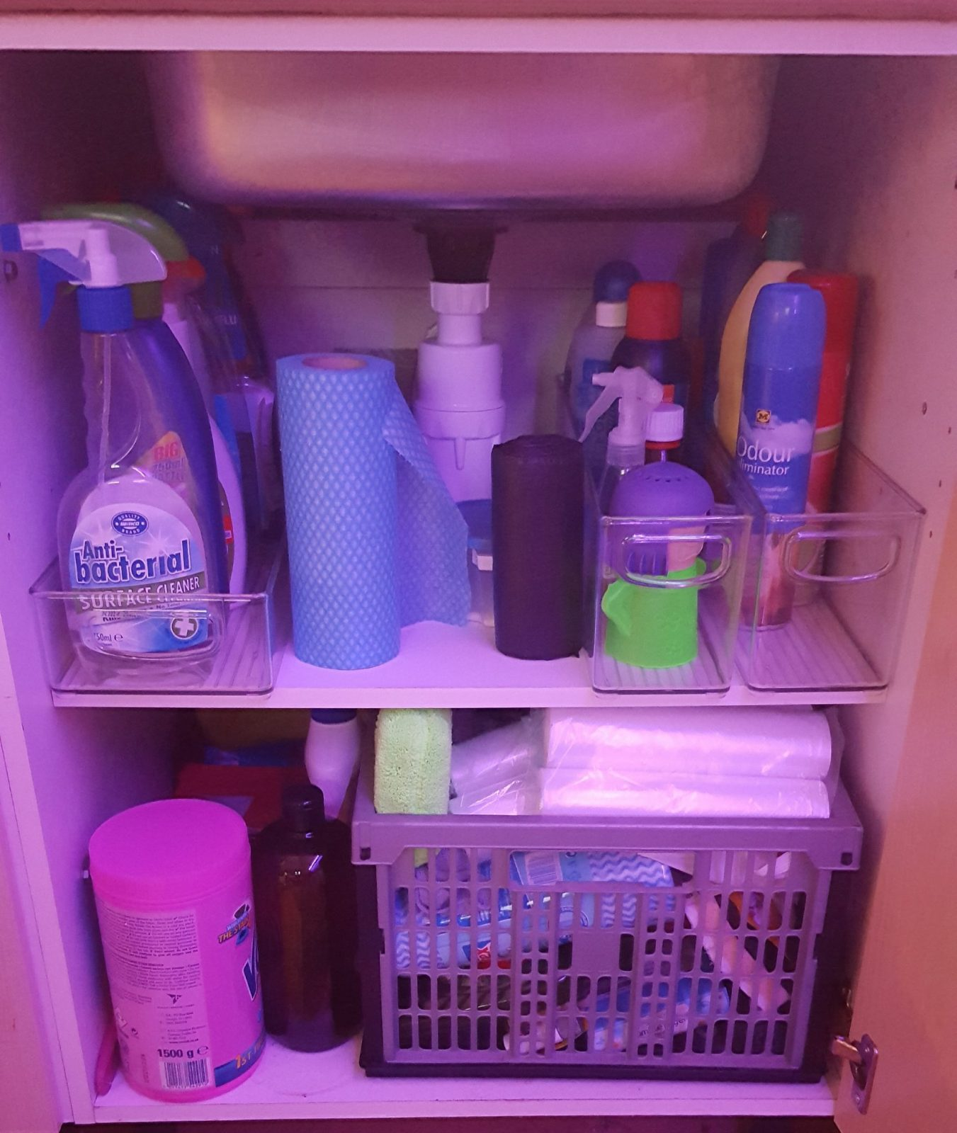 The Cupboard underneath the kitchen sink, the top shelf has been organised into containers the bottom shelf has a crate stuck in there