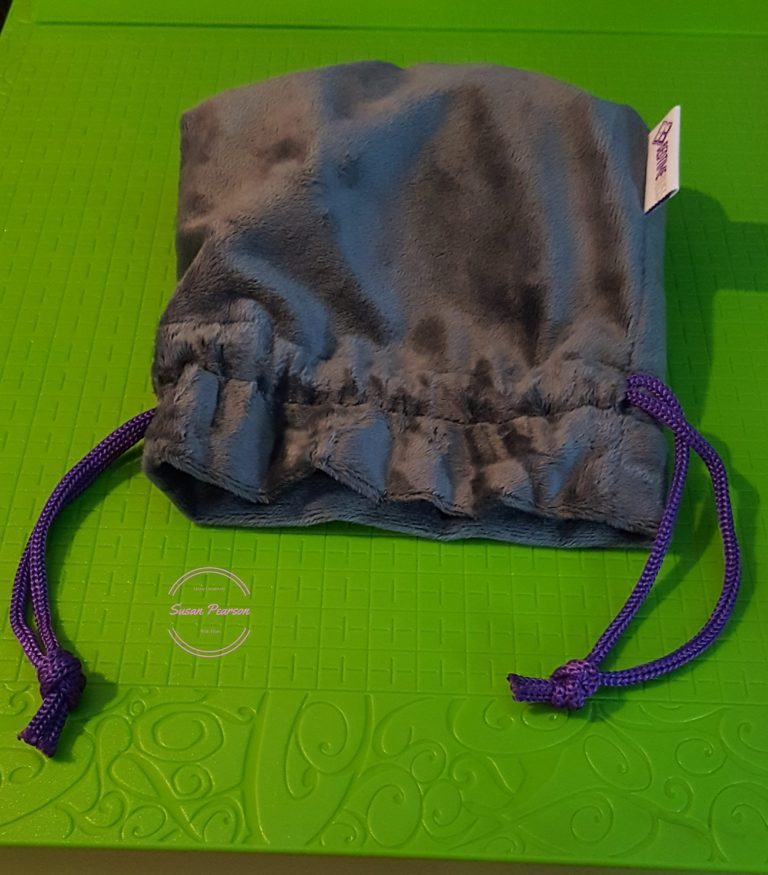 Living Creatively with Fibro | The pouch that the Bedtime Bliss Travel Pillow comes in it is grey with a purple cord