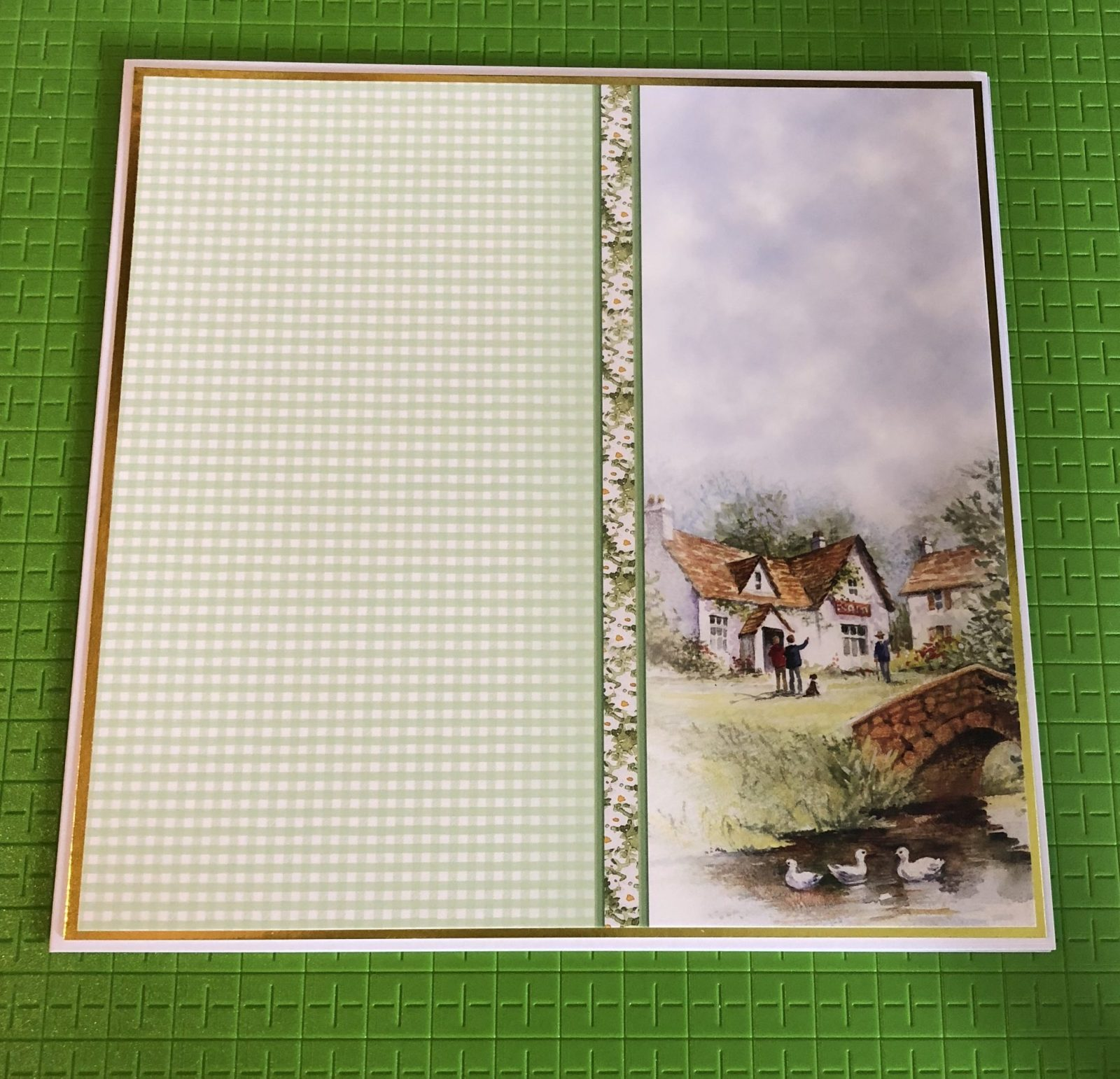 Living Creatively with Fibro | Card Base Layer with the matching cardstock featuring a green gingham check panel and an image of a county cottage with a bridge over a stream and ducks floating by