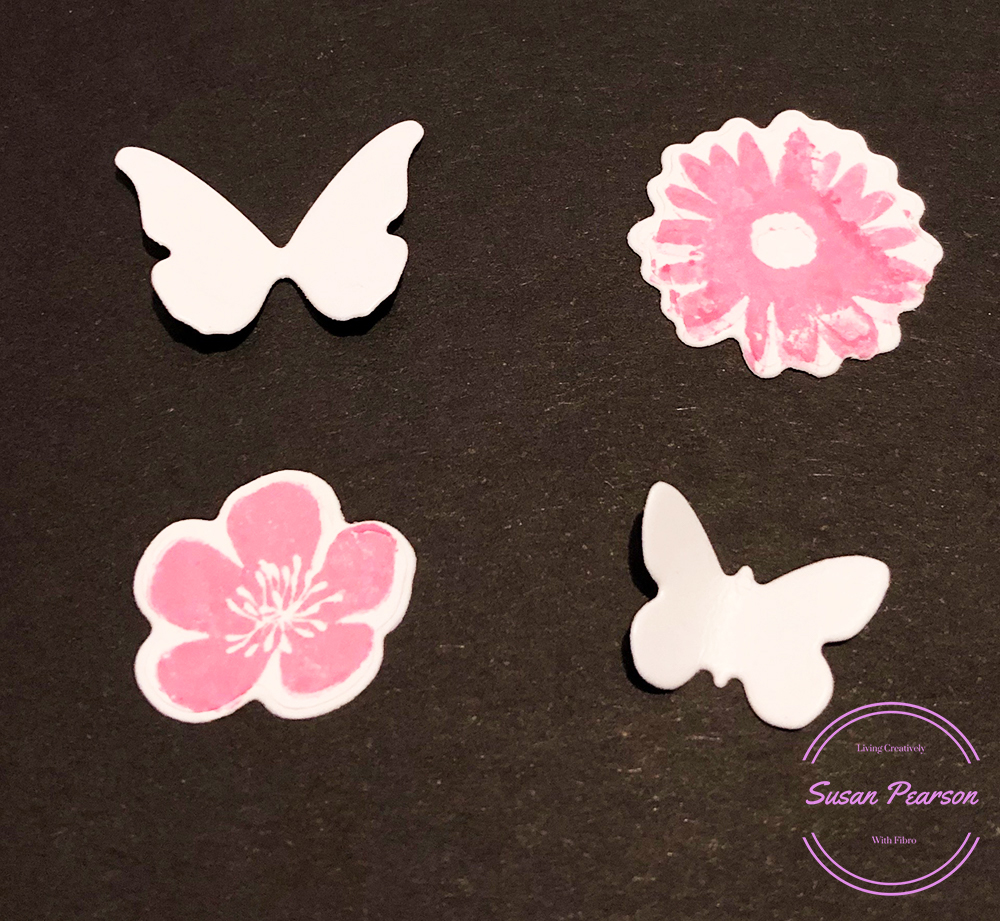 The Four die cuts, two white butterflies and two white flowers stamped pink.
