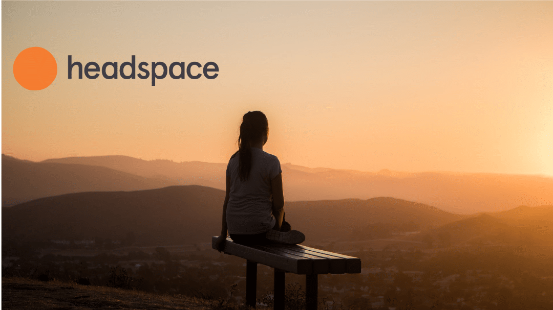 An image of a woman sitting looking out over a beautiful sunset with the Headspace Logo