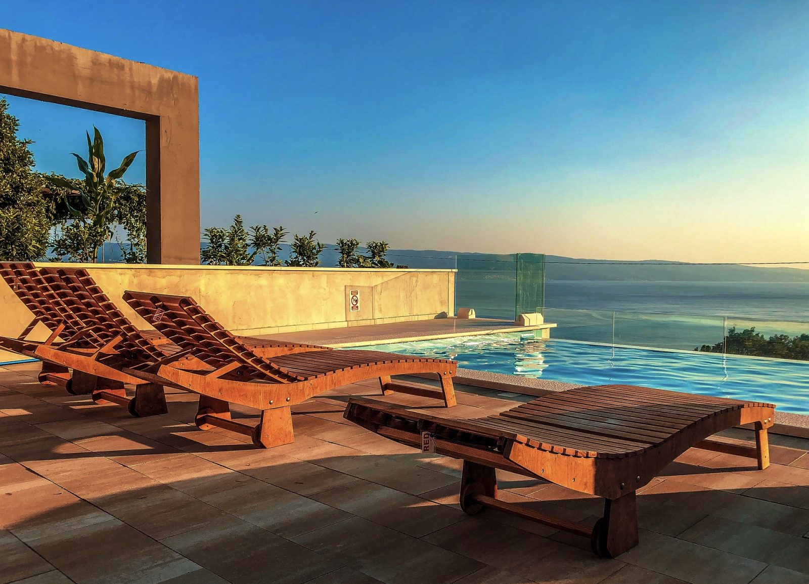 Sun loungers by an affinity pool looking out over an ocean.