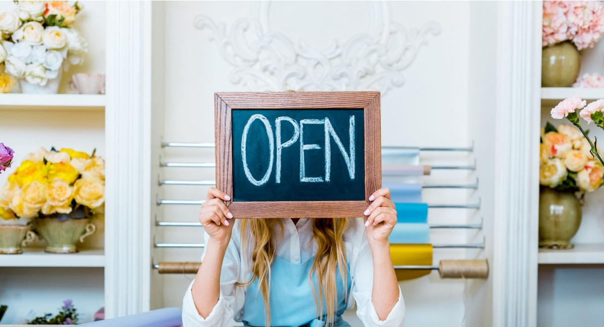 Self Employed image showing a woman holding up a blackboard with the word open in a pretty shop